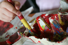 Child with paint brush. Close up of child holding paint brush and mixing colors Royalty Free Stock Image