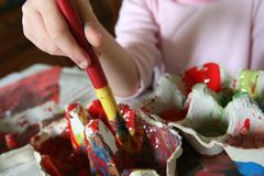 Child with paint brush. Close up of child holding paint brush and mixing colors Stock Photography