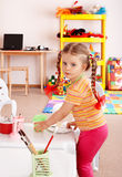 Child with paint and brush in playroom. Royalty Free Stock Images
