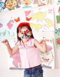 Child with paint of face in play room. Stock Photos