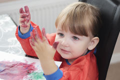 Child with paint on her hands. Preschool girl looking at her paint covered hands in fascination Stock Photos