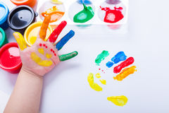 Child paint her palm with smiling face various colors. Studio sh Royalty Free Stock Images