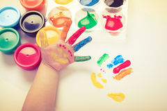 Child paint her palm with smiling face various colors. Studio sh. Child paint her palm with smiling face various colors using multicolored drawing tools. Studio stock photo
