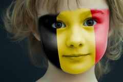 Child with a painted flag of Belgium. Portrait of a child with a painted flag of Belgium on her face, closeup Royalty Free Stock Photo