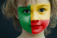 Child with a painted flag of Benin. Portrait of a child with a painted flag of Benin on her face, closeup Stock Photo