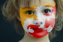 Child with a painted flag of Bhutan. Portrait of a child with a painted flag of Bhutan on her face, closeup Stock Photo