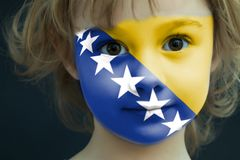 Child with a painted flag of Bosnia-Herzegovina. Portrait of a child with a painted flag of Bosnia-Herzegovina on her face, closeup Stock Image