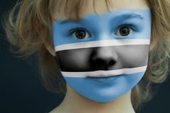 Child with a painted flag of Botswana. Portrait of a child with a painted flag of Botswana on her face, closeup Stock Images