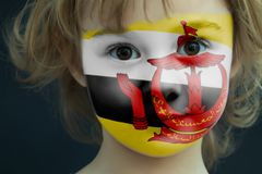 Child with a painted flag of Brunei. Portrait of a child with a painted flag of Brunei on her face, closeup Stock Photos