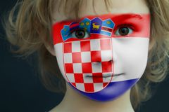 Child with a painted flag of Croatia. Portrait of a child with a painted flag of Croatia on her face, closeup Stock Image