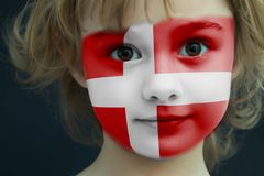 Child with a painted flag of Denmark. Portrait of a child with a painted flag of Denmark on her face, closeup Stock Images