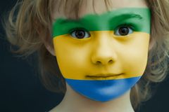 Child with a painted flag of Gabon. Portrait of a child with a painted flag of Gabon on her face, closeup Royalty Free Stock Images
