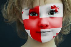 Child with a painted flag of Georgia. Portrait of a child with a painted flag of Georgia on her face, closeup Stock Photo