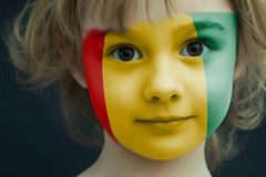 Child with a painted flag of Guinea. Portrait of a child with a painted flag of Guinea on her face, closeup Royalty Free Stock Photo