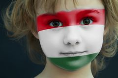 Child with a painted flag of Hungary. Portrait of a child with a painted flag of Hungary on her face, closeup Royalty Free Stock Image