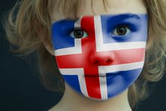 Child with a painted flag of Iceland. Portrait of a child with a painted flag of Iceland on her face, closeup Royalty Free Stock Photo