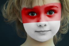 Child with a painted flag of Indonesia. Portrait of a child with a painted flag of Indonesia on her face, closeup stock photo