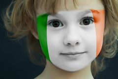 Child with a painted flag of ireland. Portrait of a child with a painted flag of ireland on her face, closeup Royalty Free Stock Photos