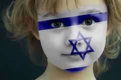 Child with a painted flag of Israel. Portrait of a child with a painted flag of Israel on her face, closeup Stock Photos