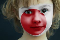 Child with a painted flag of Japan. Portrait of a child with a painted flag of Japan on her face, closeup Royalty Free Stock Photo