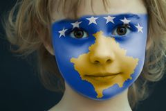 Child with a painted flag of Kosovo. Portrait of a child with a painted flag of Kosovo on her face, closeup Royalty Free Stock Images
