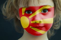 Child with a painted flag of Macedonia. Portrait of a child with a painted flag of Macedonia on her face, closeup Stock Photos