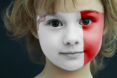 Child with a painted flag of Malta. Portrait of a child with a painted flag of Malta on her face, closeup Royalty Free Stock Photos