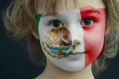 Child with a painted flag of Mexico. Portrait of a child with a painted flag of Mexico on her face, closeup Stock Photo