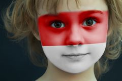 Child with a painted flag of monaco. Portrait of a child with a painted flag of monaco on her face, closeup Stock Photo