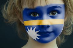 Child with a painted flag of Nauru. Portrait of a child with a painted flag of Nauru on her face, closeup Stock Photography