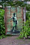 Child painted on a rusty iron door, in green, white, black and brown colors that combine with the green background of the plants a royalty free stock image