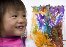 Child Painting 1. A young girl shows off her creation with pride royalty free stock photo