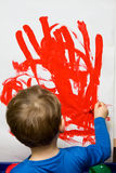 Child painting. On white paper with red paint Stock Photos