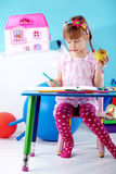 Child painting. In her nursery at home Stock Image