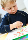 Child painting. Focused 4 year old boy painting at home stock photos