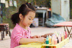 Child painting. Chinese little girl painting in the park Stock Photography