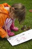 Child painting. A toddler girl painting paper and pine-cones with water colors Stock Image
