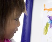 Child Painting 4. A young preschool girl concentrates as she paints a picture royalty free stock images