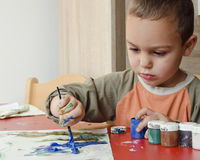Child painting with brush and colors Royalty Free Stock Photo