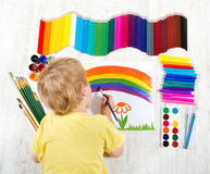 Child painting with brush, a lot of paints Royalty Free Stock Photo