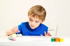 Child painting a ceramic pottery model at art class. Art school. Creative education and development. Child painting in the. Kindergarten. Cute little boy royalty free stock photos