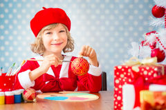 Child painting Christmas decorations Stock Photography