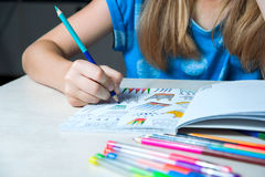 Child painting a coloring book. New stress relieving trend. Stock Photos