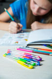 Child painting a coloring book. New stress relieving trend. Royalty Free Stock Photo