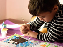 Child painting. Cute child with concentrating expression painting a winter landscape Royalty Free Stock Photos