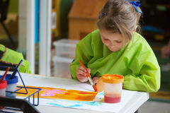 Child painting. A drawing with colourful brushes at school or preschool Stock Photos