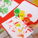 Child painting a drawing with finger paints Stock Photos
