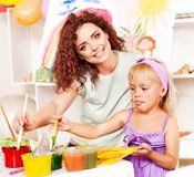 Child painting at easel. Child and teacher painting at easel in school Royalty Free Stock Images