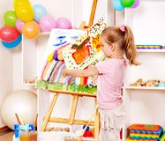 Child painting at easel. Royalty Free Stock Image