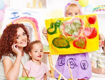 Child painting at easel. Child girl and teacher painting  in school Royalty Free Stock Images